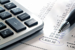 Financial Budget Statement with Calculator and Pen. Calculator and ink pen on a financial account statement with check marks on numbers and total circled for Stock Photo