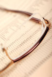 Financial business concept. Macro of financial data through eyeglasses, laying on newspaper Royalty Free Stock Photography