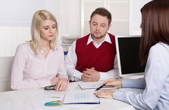 Financial business meeting: young married couple - adviser and c. Lients sitting at desk Stock Photos