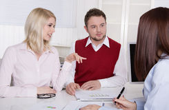 Financial business meeting: young married couple - adviser and c. Lients sitting at desk Royalty Free Stock Image