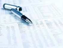 Financial business pen on currencies newspaper Stock Photo