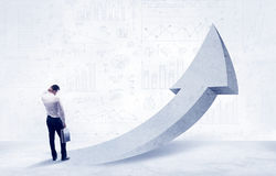 Financial businessman with arrow concept. Young sales business person in elegant suit standing with his back in front of a big arrow pointing up and a clear royalty free stock photography