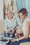 Positive smart women doing calculations. Financial calculations. Positive smart women sitting together while doing financial calculations stock photos