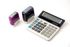 Financial calculator and two stamps. Photographed on white background Stock Image