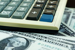 Financial calculator on US dollar banknote, focus on blank blue Royalty Free Stock Photos