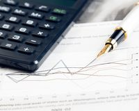 Financial chart and graph near pen and calculator Royalty Free Stock Photography