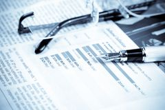 Financial chart and graph near pen and glasses Stock Images
