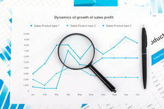 Financial chart with a magnifying glass. Report on Stock Photo