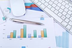 Financial chart paper, pen, keyboard and mouse.  stock photo