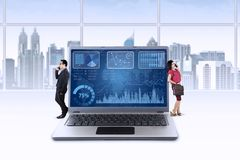 Financial chart and two businesspeople Royalty Free Stock Photo