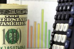 Financial Chart and US Currency One Hundred Dollar. Bills. This photo conveys financial management concepts such as, inflation, budget reduction, cost cutting Stock Images