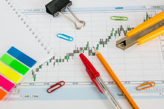 Financial chart on a white background, coins, pens, pencils and paper clips. Financial chart on a white background, coins, pens, pencils, paper clips Stock Photo
