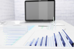 Financial charts on the desktop and laptop screen Royalty Free Stock Image