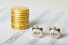 Financial charts, coins and dice cubes with words Sell Buy. Sele Stock Photos