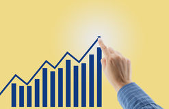 Financial charts showing growing revenue with finger hand Stock Images