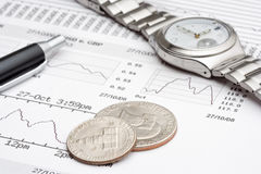 Financial charts, some change and an expensive watch Stock Image