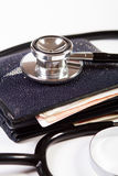 Financial checkup. Conceptual photo: financial checkup, a stethoscope on black wallet Royalty Free Stock Photography