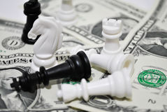 Financial chess. Various chess figures on dollar bills stock photography