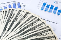 Financial concept. Stack of dollars over financial reports Stock Image