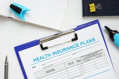 Free Financial Concept About HEALTH INSURANCE PLANS With Sign On The Bank Form Stock Photos - 219740963