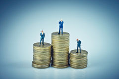 Financial concept. Business people standing on coins piles Royalty Free Stock Image