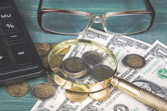 Financial concept. Calculator, magnifying glass, euro coins, british penny, dollar bills and glasses on green wood table Royalty Free Stock Image