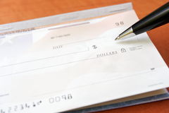 Financial concept check and pen Stock Photo