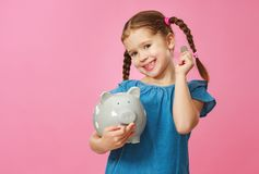 Financial concept of children`s pocket money. child girl with piggy Bank      on a colored pink background royalty free stock photo