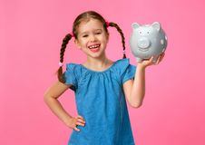 Financial concept of children`s pocket money. child girl with piggy Bank      on a colored pink background royalty free stock photography