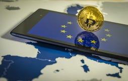 Financial concept with golden Bitcoin over smartphone, EU flag and map. Stock Photos