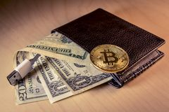 Financial concept with golden Bitcoin over a wallet with US dollars and USB cable royalty free stock photos