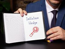 Financial concept about Inflation Hedge with inscription on blank notepad