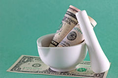 Financial concept - money in mortar with pestle Stock Images