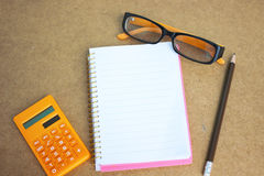 Financial concept with Notebook, eyeglass and calculator on wooden background. Financial concept with Notebook, eyeglass and calculator stock photography