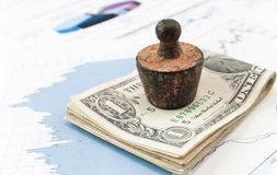Financial concept. Old rusty weight on money Royalty Free Stock Photos