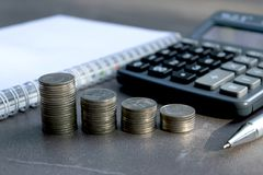 Financial  concept, Pen and calculator with coins  graph paper o. N the table Stock Images
