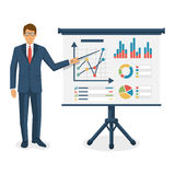 Financial consultant concept. Consultant businessman near blackboard holding a pointer in hand, training. Research graphs market, diagrams, charts financial Stock Photos