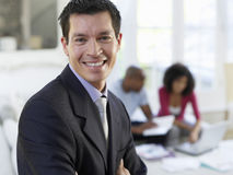 Financial Consultant With Couple In Background Stock Photo