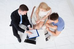 Financial consultant presenting new project investment to couple. High angle view of financial consultant presenting new project investment to young couple in royalty free stock photography