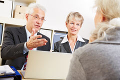 Financial consultants talking. Two financial consultants talking to a senior women in a bank Stock Photo