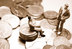 Financial counselling. Miniature figurines on a pile of coins asking for financial advice Royalty Free Stock Photos