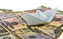 Financial Course. A paper boat made of a page from school notebook on the money Royalty Free Stock Photography