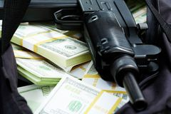 Financial crime. Close-up of black weapon lying on heap of hundred dollar bills Stock Image