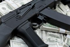 Financial crime. Close-up of black weapon lying on heap of hundred dollar bills Stock Photos