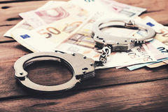 Financial crime concept - money and handcuffs on the table. Financial crime concept - money and handcuffs on the brown wooden table Royalty Free Stock Image