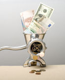 Financial crisis. Denominations dollars and euro in an old metal meat grinder Royalty Free Stock Photography