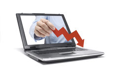Financial crisis. A Hand reaches out of an Laptop with a downwards graph Royalty Free Stock Images