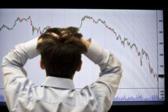 Financial Crisis. Frustrated broker looking at the falling graph of a stock market struck in financial crisis Stock Photos
