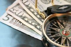 Financial crisis. Navigating compass against dollars and euro Royalty Free Stock Photos