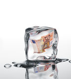 Financial crisis. Euro banknote frozen in ice cube, financial crisis concept Stock Photos